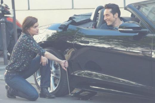 Casal. Ela troca o pneu, ele está dentro do carro.