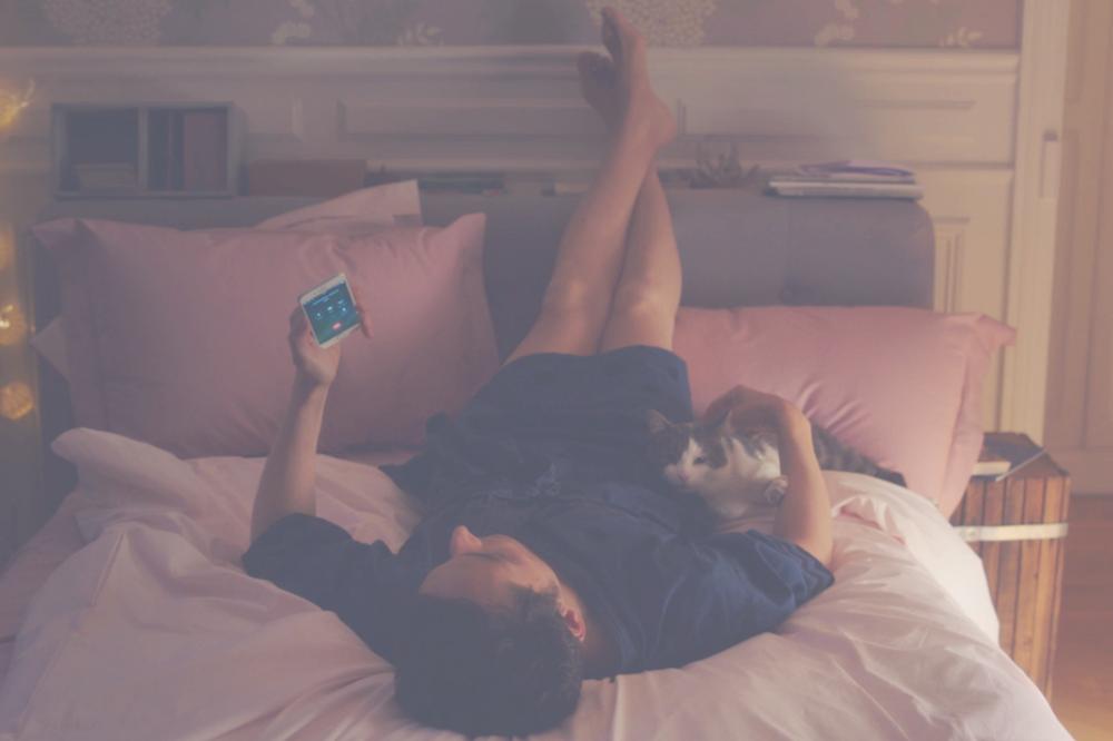 Homem na cama com celular e gato