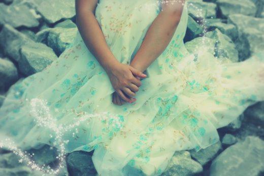 Menina sentada em chão de pedras, sozinha, com vestido que lembra os dos contos de fadas. Aparece apenas a metade inferior do seu corpo.